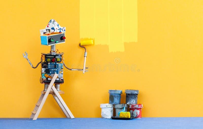 O robô do decorador repinta a parede da sala na cor amarela Brinquedo engraçado do robô do pintor e dentro redecoração interior imagens de stock royalty free