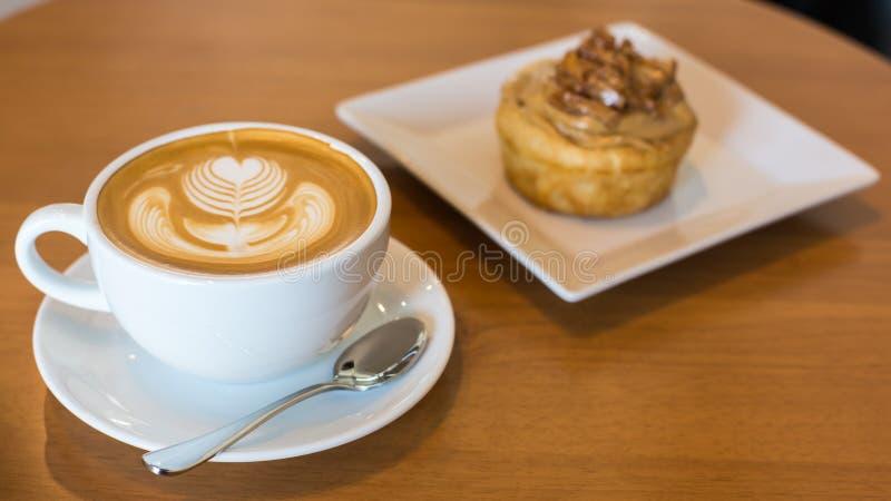 O rolo de canela de Apple serviu com café do latte na tabela imagens de stock royalty free
