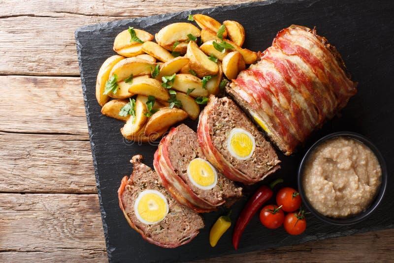 O rolo de carne cortado delicioso envolvido no bacon com batata firma a imagem de stock