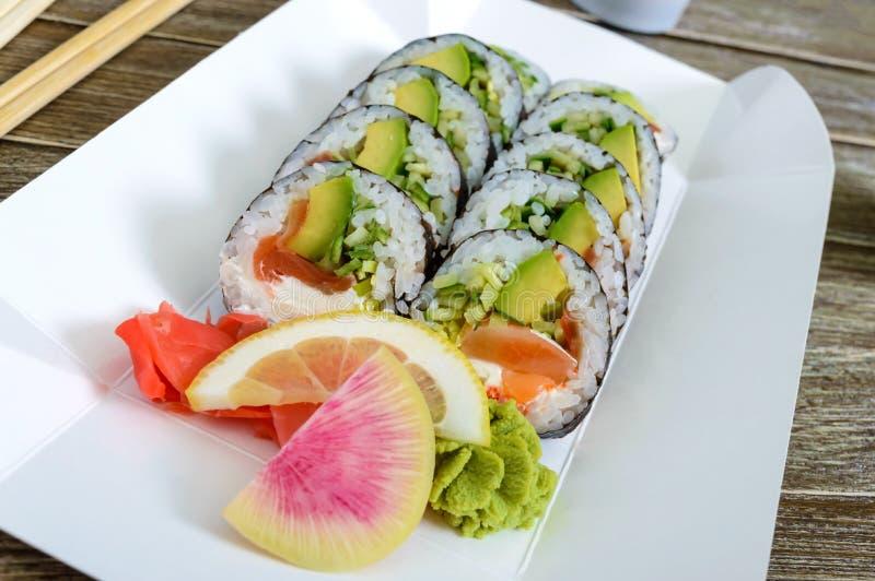 O rolo de sushi com salmões, abacate, queijo creme, alho-porro, pepino, caviar do tobiko, serviu em uma placa de papel fotos de stock