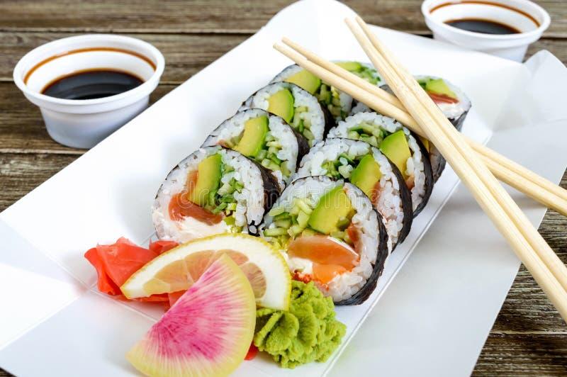 O rolo de sushi com salmões, abacate, queijo creme, alho-porro, pepino, caviar do tobiko, serviu em uma placa de papel Alimento d imagens de stock
