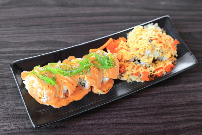 O rolo de sushi de Maki feito da parte superior salmon com alga do wakame e o sushi especial cobrem com farinha do tempura, maion fotografia de stock