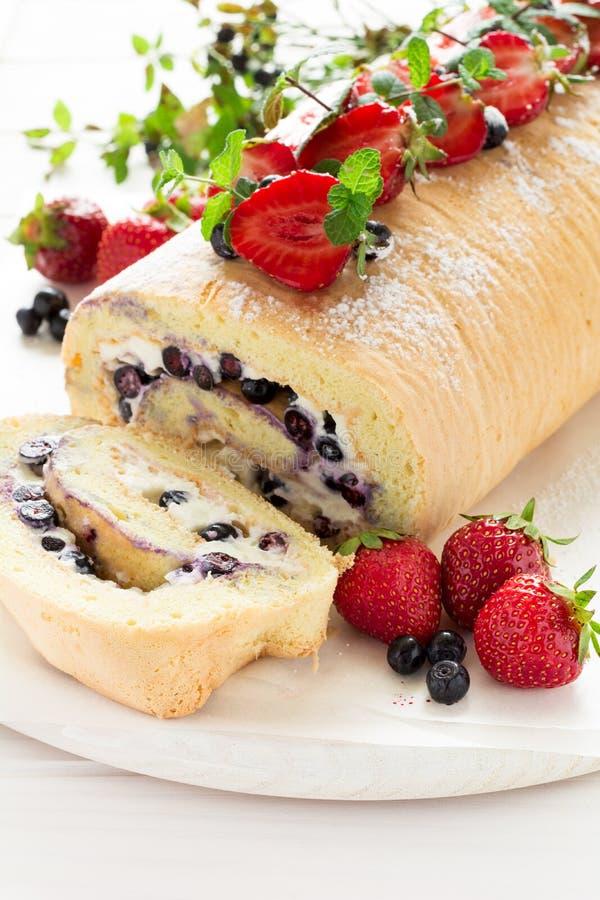 O rolo do biscoito com creme e mirtilos do mascarpone decorou morangos, mirtilos e folhas de hortelã imagem de stock