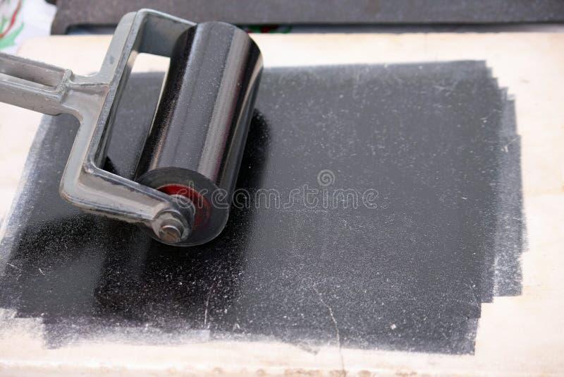 O rolo encheu-se com o de tinta preta para tomar as impressões digitais e para imprimir fotos de stock