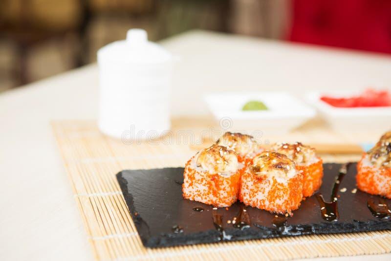O rolo japonês do sushi cobriu com fatia salmon picante no fundo escuro do grunge Rolo quente fritado com salmões, abacate, pepin imagem de stock