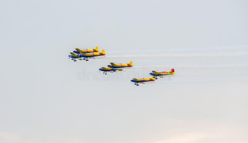 O Romanian Hawks os pilotos da equipe com seus aviões coloridos que treinam no céu azul imagem de stock