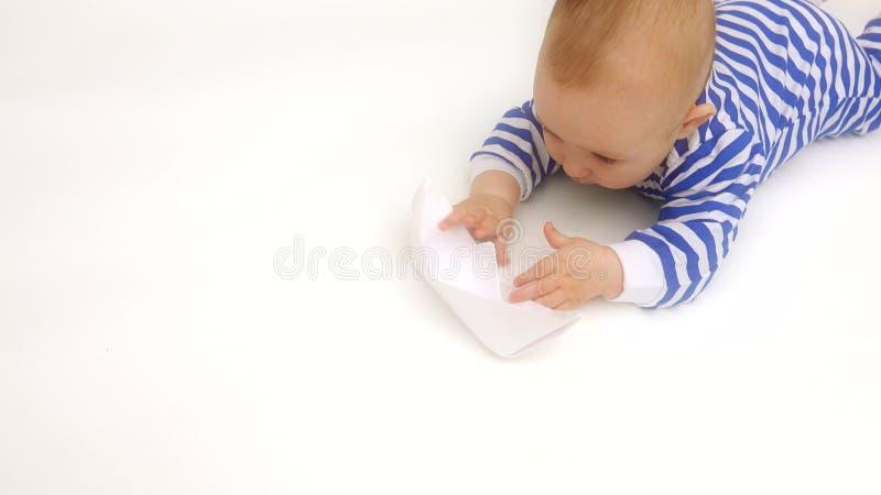 O romper listrado vestindo do bebê bonito joga com barco de papel fotos de stock royalty free