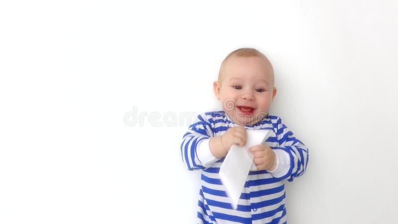 O romper listrado vestindo do bebê feliz joga com barco de papel imagens de stock