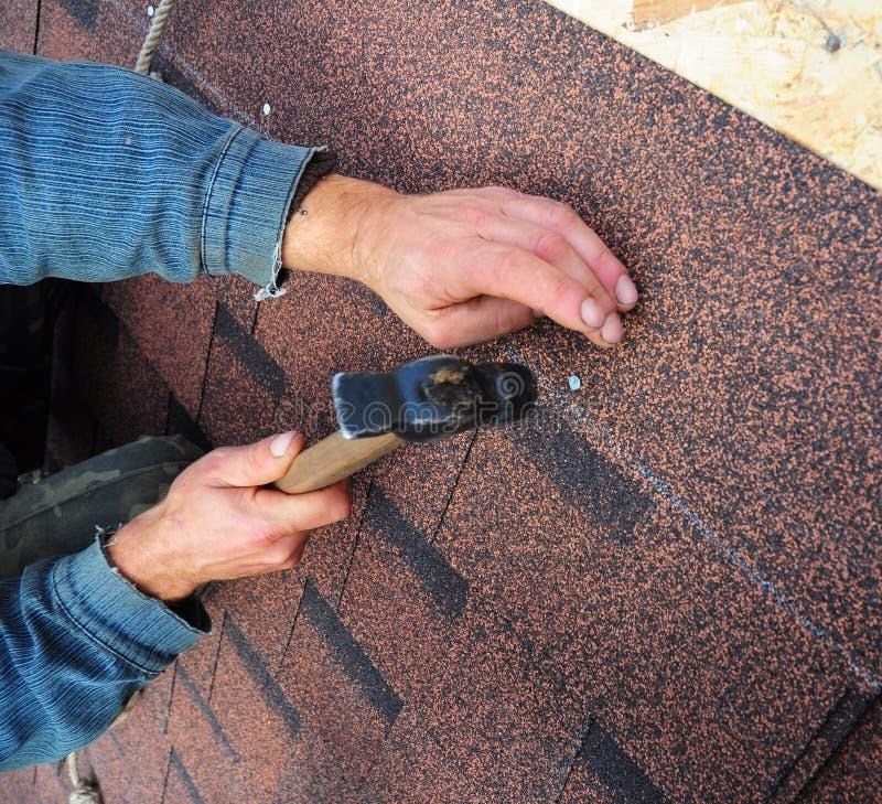 O Roofer instala as telhas do telhado do betume - close up nas mãos Roofin imagem de stock