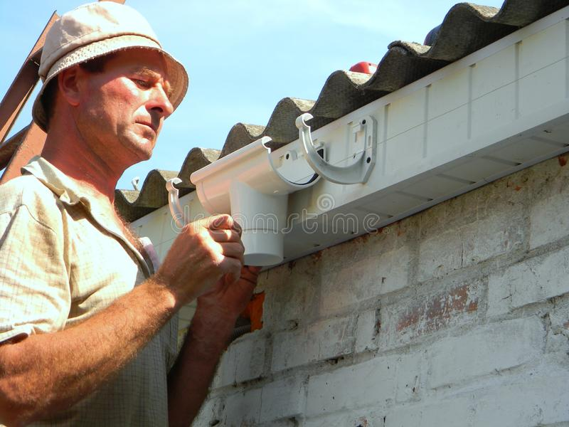 O Roofer para instalar e reparar suportes da calha chove a instalação da calha com a tubulação do downspout do dreno guttering fotos de stock royalty free