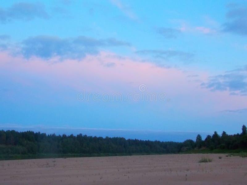 O rosa da praia da areia do rio do por do sol do céu nubla-se árvores azuis do verão foto de stock