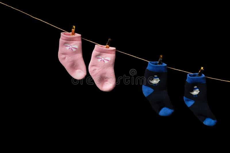 O rosa de bebê e as peúgas azuis penduram em um pino em uma corda Em um fundo preto fotografia de stock