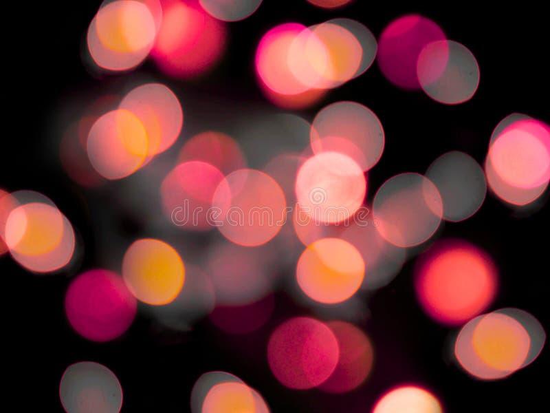 O rosa e o círculo abstrato amarelo borraram luzes em um fundo preto imagens de stock