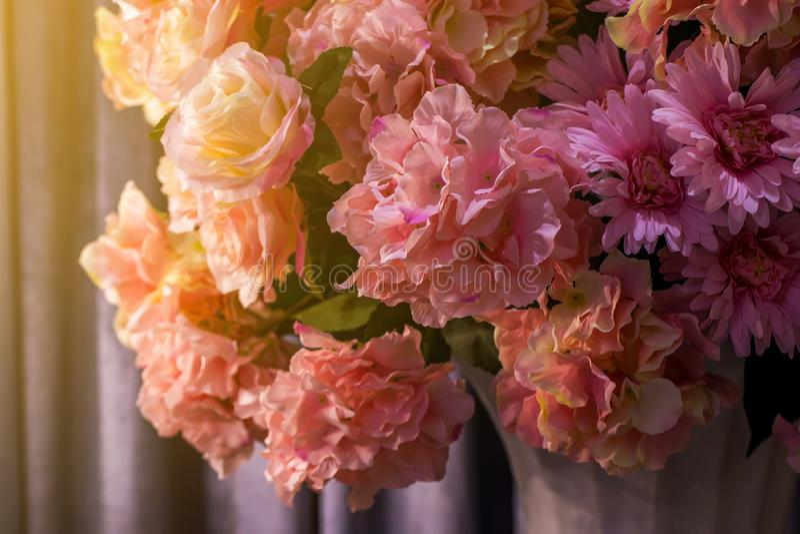 O rosa floresce na sala com a luz eletrônica com cortina cinzenta, estilo retro romântico da vela, lowkey imagens de stock