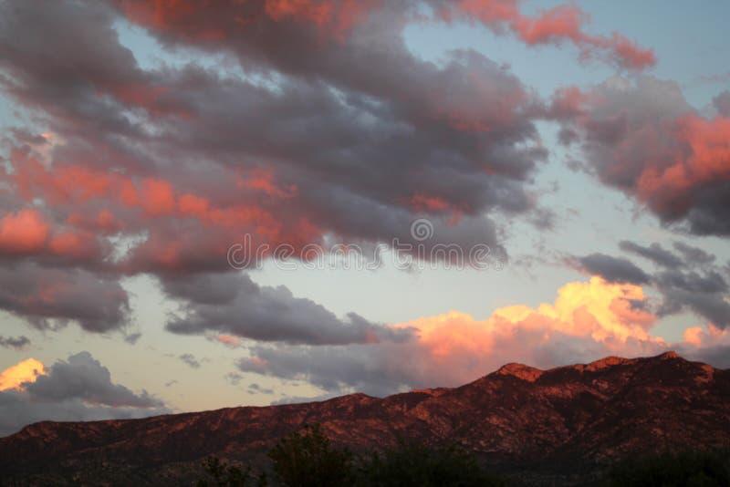 O rosa quente impressionante nubla-se sobre as montanhas vermelhas no por do sol em Tucson o Arizona imagens de stock