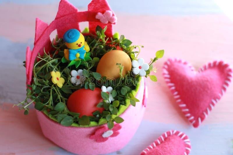 O rosa sentiu a cesta da Páscoa com ovos pintados e a galinha amarela em uma cesta em um fundo cor-de-rosa-azul Fundo feliz do di imagem de stock royalty free