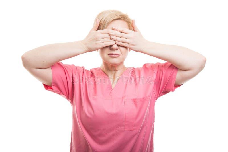 O rosa vestindo da enfermeira fêmea esfrega os olhos da coberta como o concep cego fotografia de stock