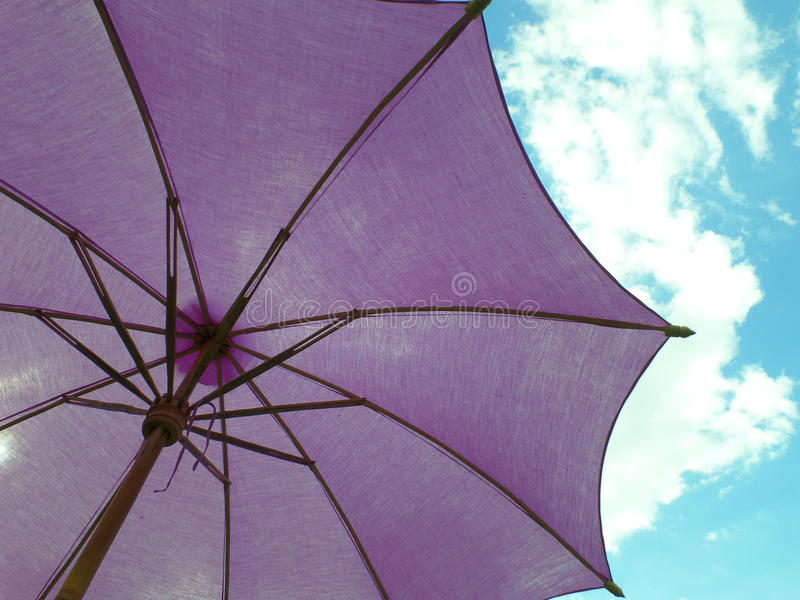 O roxo coloriu o parasol sob o céu azul vívido com nuvem branca fotografia de stock