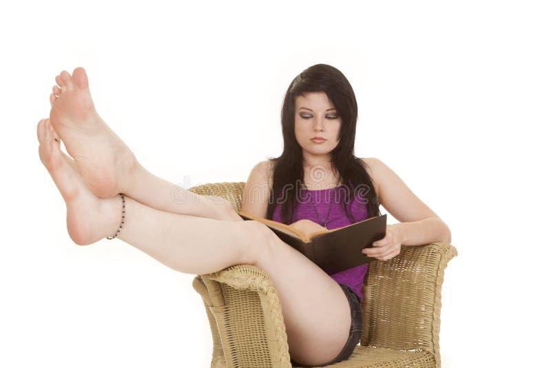O roxo da mulher na cadeira leu os pés acima imagem de stock