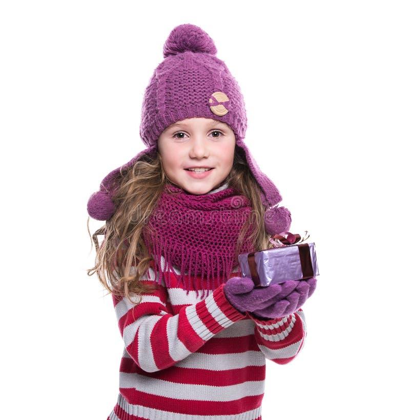 O roxo vestindo de sorriso bonito da menina fez malha o lenço, o chapéu e as luvas, guardando o presente do Natal no fundo branco imagens de stock
