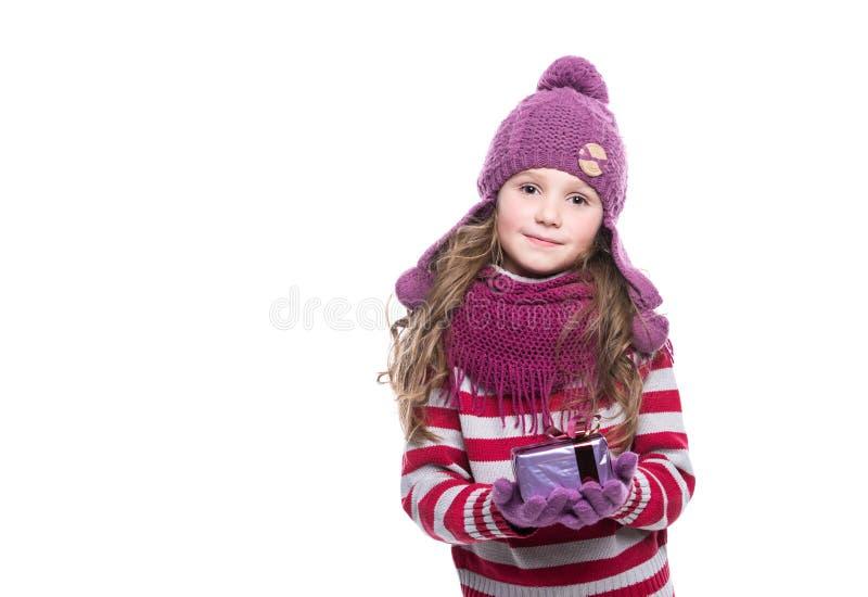 O roxo vestindo de sorriso bonito da menina fez malha o lenço, o chapéu e as luvas, mantendo o presente do Natal isolado no fundo foto de stock