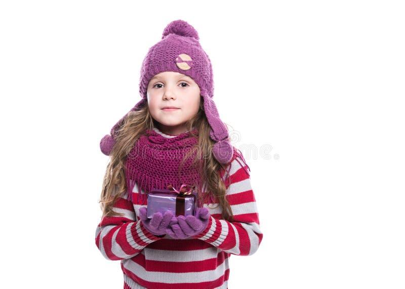 O roxo vestindo de sorriso bonito da menina fez malha o lenço, o chapéu e as luvas, mantendo o presente do Natal isolado no fundo imagens de stock