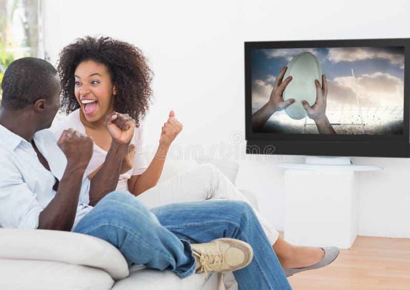 O rugby de observação dos pares entusiasmado combina na televisão na sala de visitas foto de stock