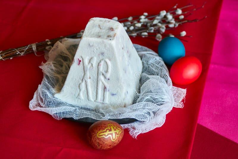 O russo festivo da Páscoa endurece dos ovos da massa e da pintura do coalho na tabela vermelha imagem de stock royalty free