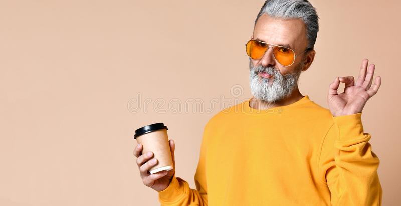 O sênior elegante do homem que olha a câmera, tendo o tampão com café nos braços e mostra uma aprovação do sinal com seus dedos imagem de stock royalty free