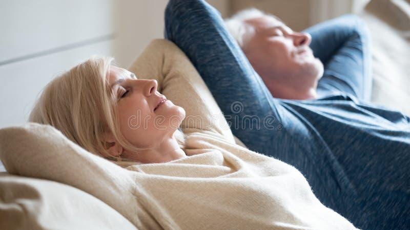 O sênior envelheceu os pares que relaxam no breathi confortável do sofá junto fotografia de stock royalty free