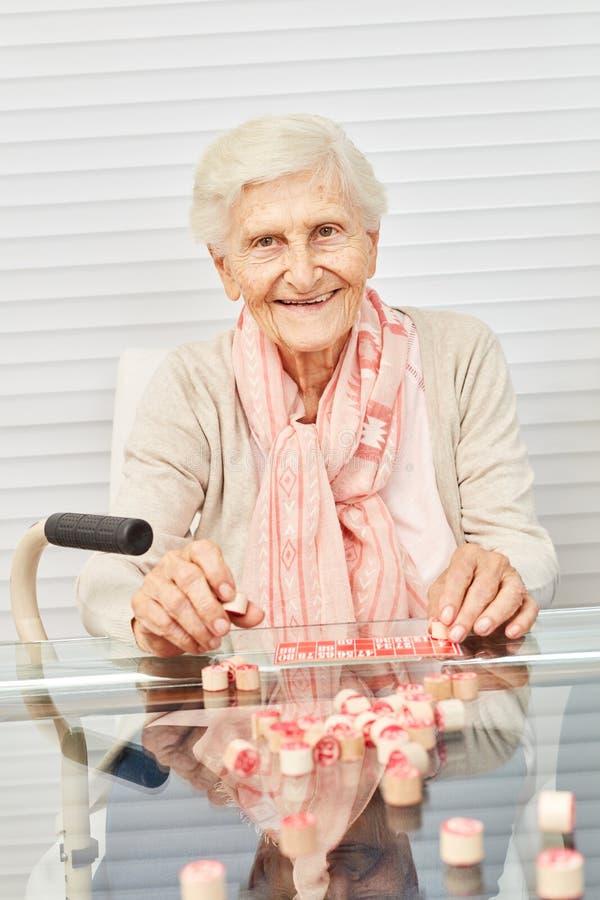 O sênior idoso tem o divertimento que joga o bingo fotos de stock royalty free