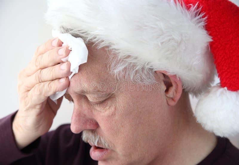O sênior no chapéu de Santa esfrega sua testa foto de stock