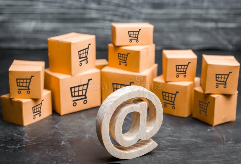 O símbolo de madeira do e-mail está perto das caixas de cartão Conceito da troca e do comércio eletrônico em linha Distribui??o e imagens de stock