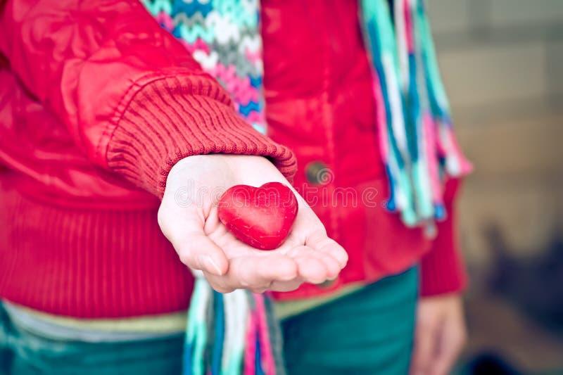O símbolo do amor da forma do coração na mulher entrega o cumprimento romântico do dia de Valentim foto de stock