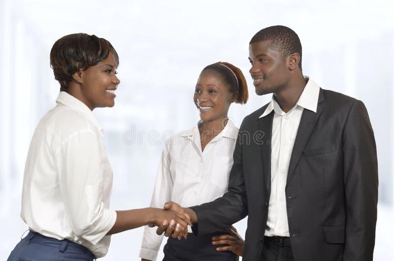 O sócio comercial de três africanos agita as mãos na reunião fotografia de stock royalty free