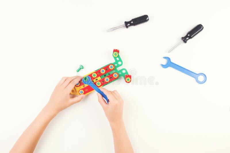 O ` s da criança entrega o jogo com as ferramentas coloridas dos brinquedos no fundo branco Vista superior foto de stock