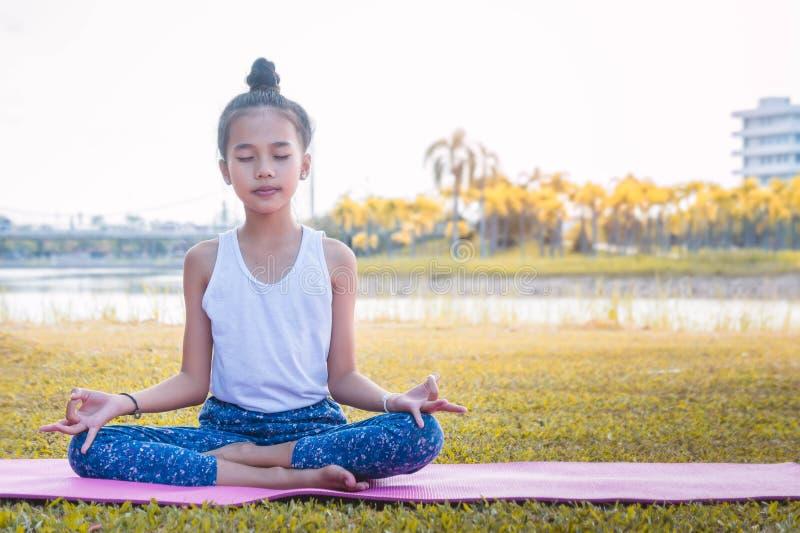 O ` s da menina feliz e medita sobre a prática da ioga no parque fotos de stock royalty free