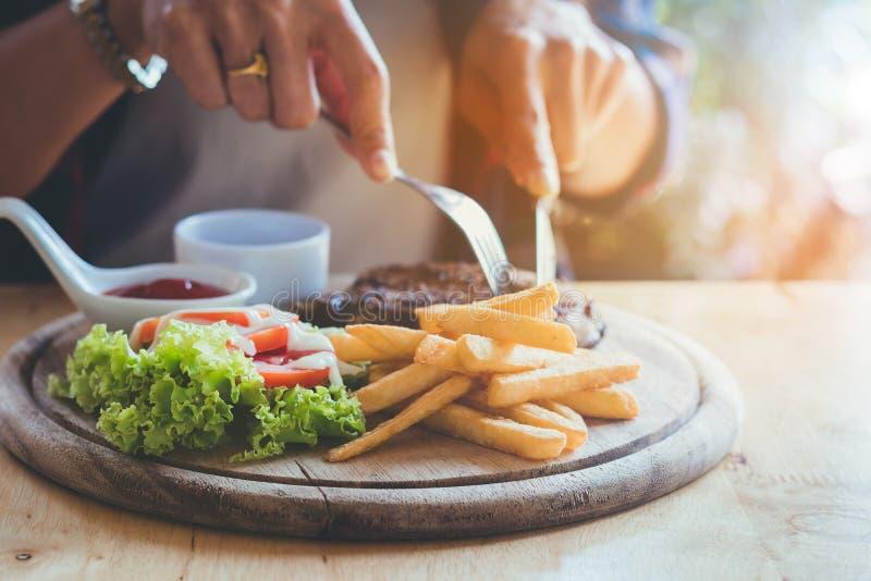 O ` s da mulher de Ásia entrega comer o bife da carne com divertimento e feliz imagem de stock royalty free