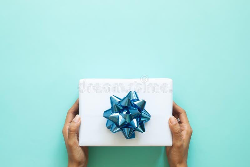 O ` s da mulher entrega guardar a caixa de presente branca com a fita azul na cor pastel fotografia de stock royalty free