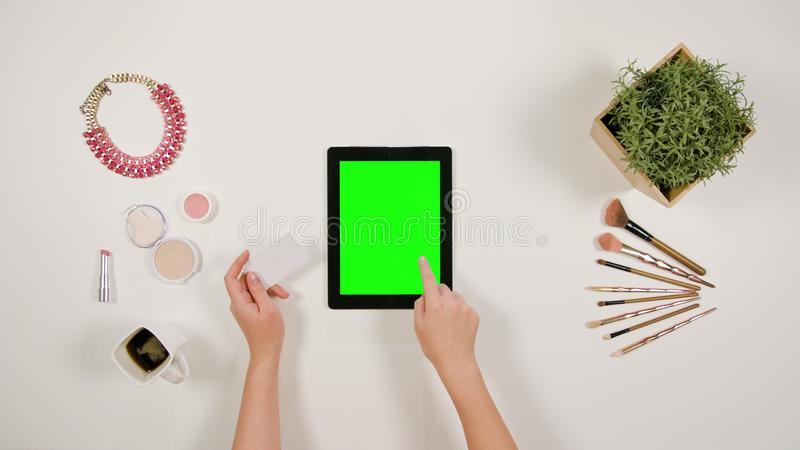O ` s da senhora entrega o toque de uma tabuleta e guardar um cartão fotografia de stock