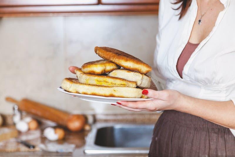 O ` s das mulheres entrega guardar a placa dos bolos com vista lateral foto de stock royalty free