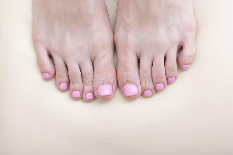 O ` s das mulheres toes o close-up Pedicure cor-de-rosa Fundo branco foto de stock