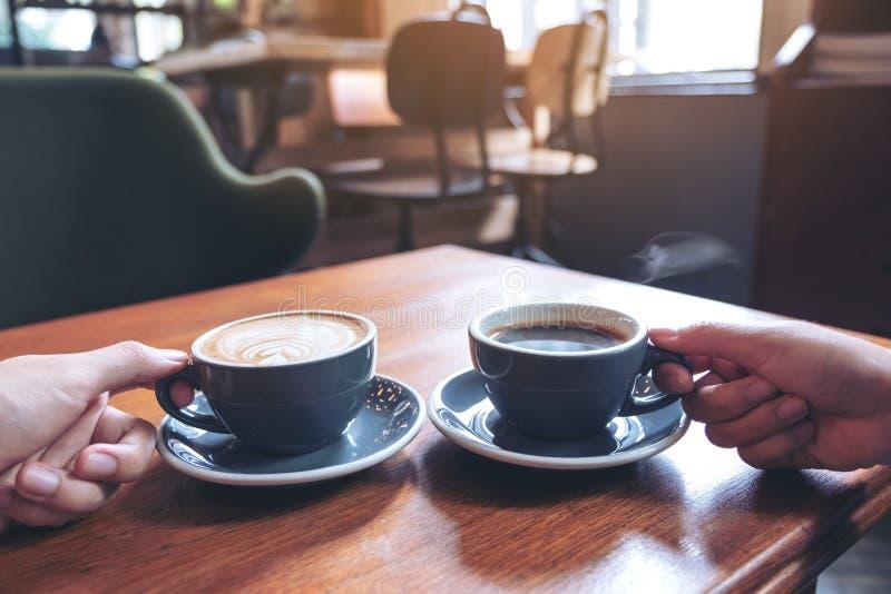 O ` s de dois povos entrega guardar copos do café e do chocolate quente na tabela de madeira no café imagem de stock royalty free