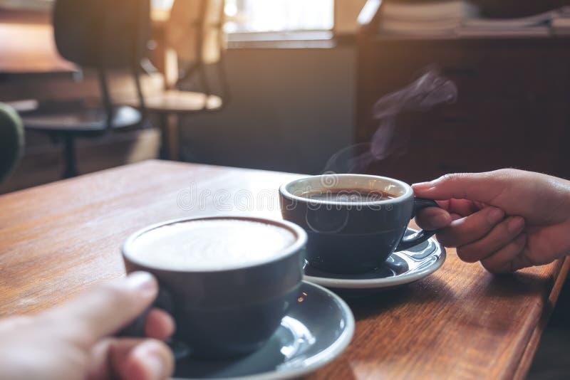 O ` s de dois povos entrega guardar copos do café e do chocolate quente na tabela de madeira no café fotografia de stock royalty free