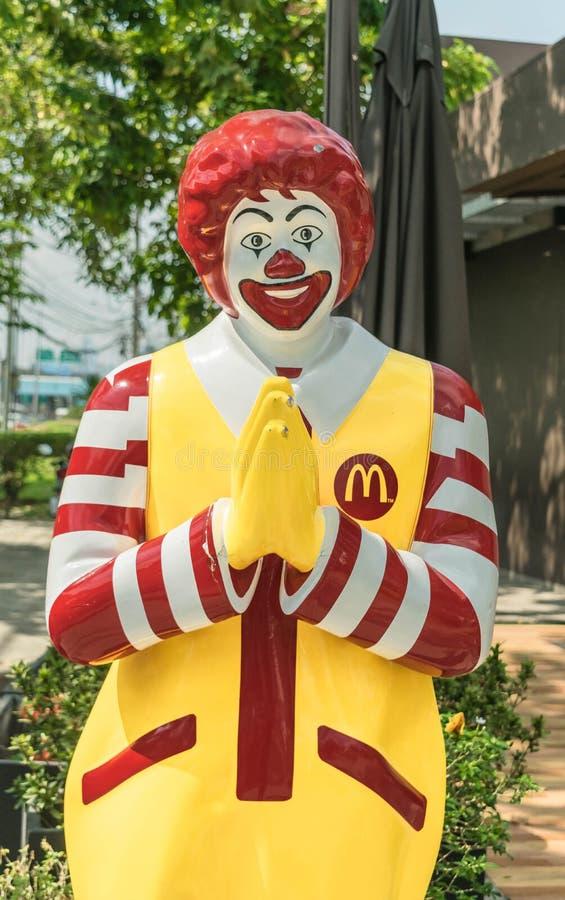 O ` s de McDonald do restaurante dos símbolos da mascote em Tailândia a estátua levanta o estilo tailandês ou o Wai do respeito foto de stock royalty free