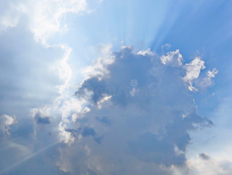 O ` s de Sun irradia o estouro através das nuvens no céu azul imagem de stock royalty free