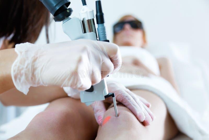 O ` s do esteticista entrega a remoção do cabelo do pé com um laser a seu cliente no salão de beleza fotografia de stock