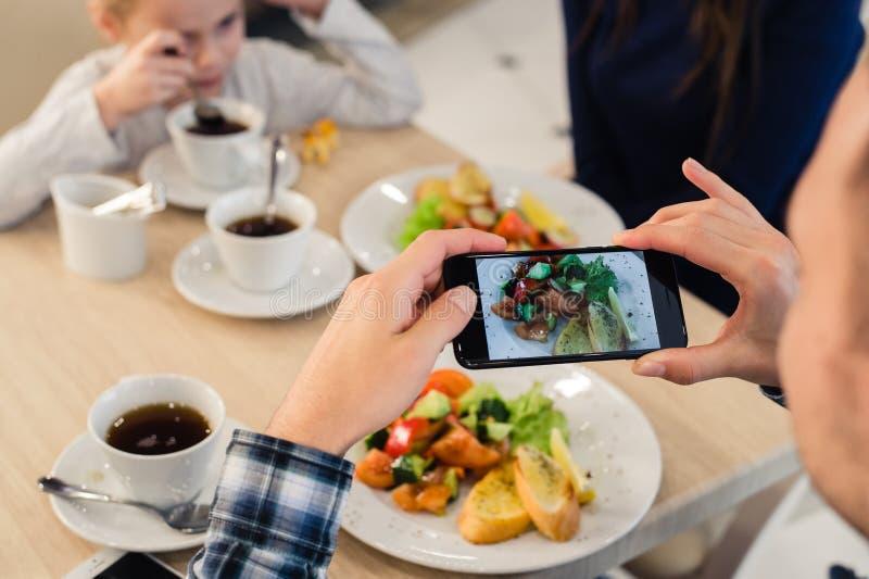 O ` s do homem do close-up entrega a tomada da imagem do alimento com o telefone esperto móvel foto de stock