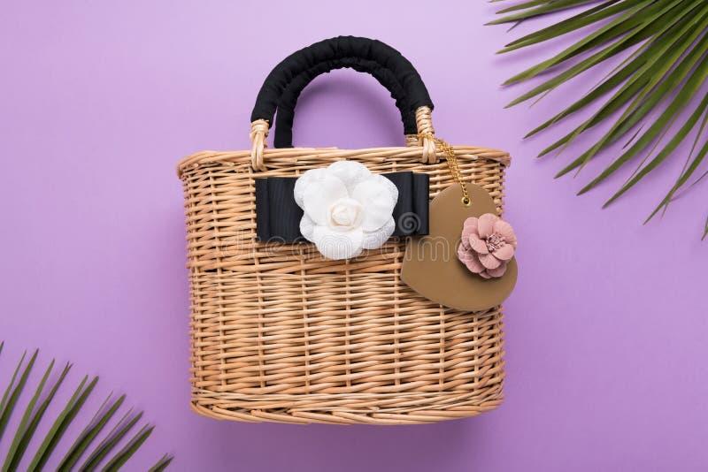 O saco da mulher de vime da forma no fundo, no fim acima, no curso e nas férias violetas ou roxos conceito, vista superior, conce imagens de stock royalty free