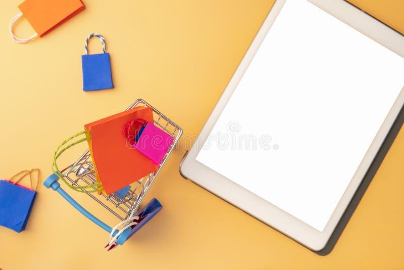 O saco de compras e o trole de papel coloridos vão para baixo de flutuar o fundo cor-de-rosa para o espaço da cópia foto de stock royalty free